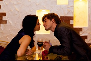 Young happy couple romantic kissing date with glass of red wine at restaurant, celebrating valentine day kiss low natural candle light