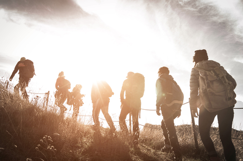 group of hikers trekking in the sunshine