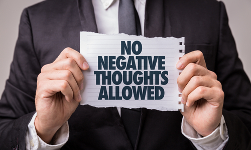 man holding sign no negative thoughts allowed