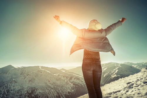 woman extending arms during sunrise on mountain summit