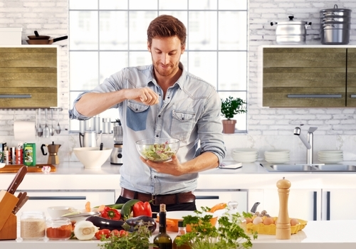 handsome man preparing meal in kitchen content with Progentra