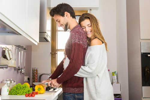 man preparing meal in kitchen hugged by wife and happy with Progentra