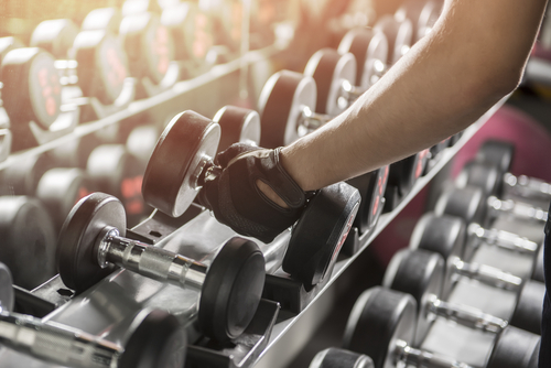 woman picking up a dumbbell in the gym