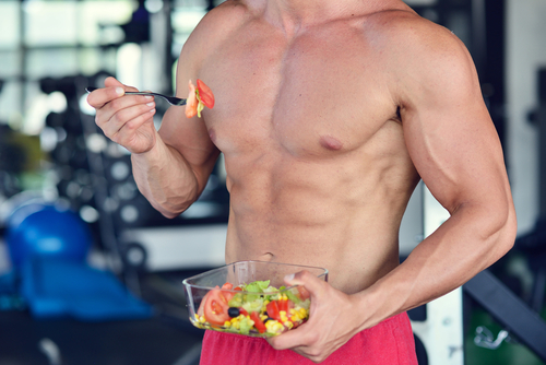 muscular guy eating salad in gym and takes Progentra after