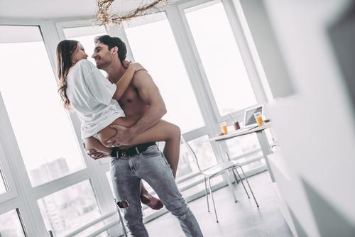 shirtless man lifting woman grabbing butt
