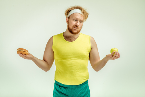 overweight guy choosing between apple and burger