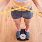 fit woman measures waist and steps on scale