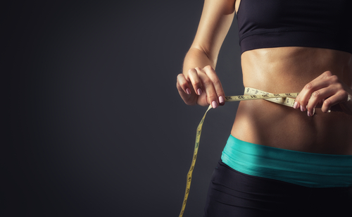 fit woman measures waist using tape