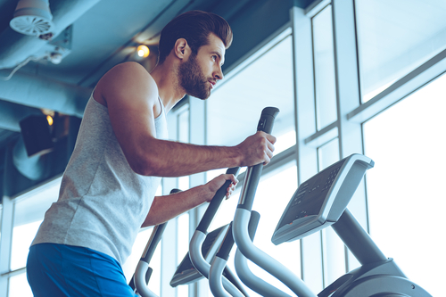fit man who takes Progentra regularly exercising on elliptical