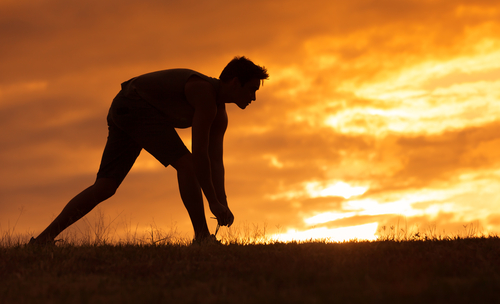 man getting ready for a run during sunset and takes Progentra