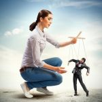woman controlling man on strings like a puppeteer