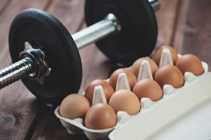 tray of eggs and dumbbell, high protein, muscle