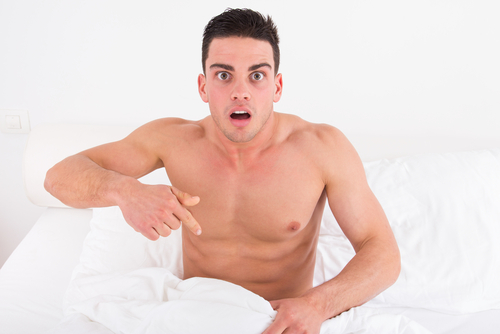 naked man in bed pointing at his crotch looking concerned