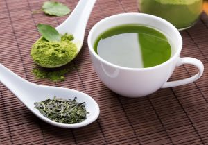 cup of green tea and green tea powder and leaves