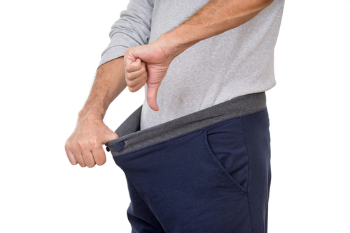 man holding out pants with thumbs down, erectile dysfunction