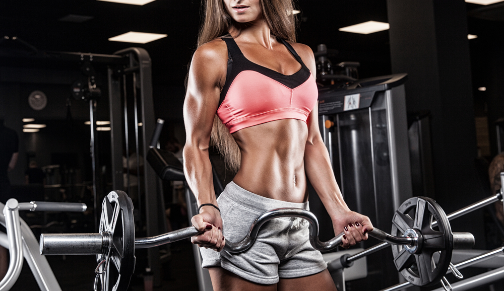 hot athletic woman carrying barbell in gym