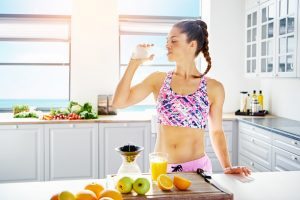 fit and healthy woman drinking lots of water with fruits