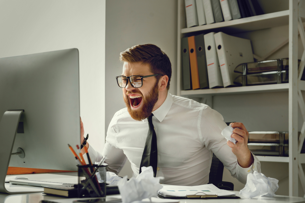 man screaming and stressed in workplace