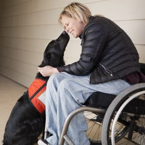 woman in wheelchair showing affection to service dog