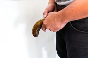 man holding an overripe limp banana against crotch, erectile dysfunction
