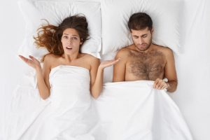 man suffering from erectile dysfunction with disappointed wife in bed