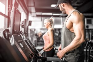 man in treadmill staring at beautiful woman at the gym