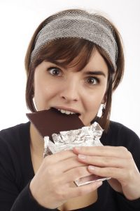 woman on her period eating chocolate