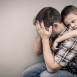 little boy hugging and comforting depressed dad