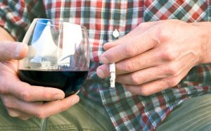man holding cigarette and glass of wine