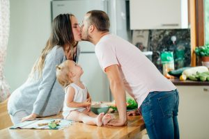 couple kissing while toddler looks Progentra helps marriage
