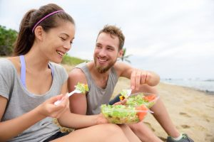 couple eating healthy salad by the beach