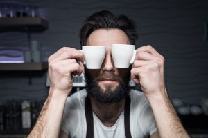 man holding espresso cups against his eyes