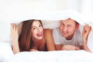 happy couple in bed under the covers