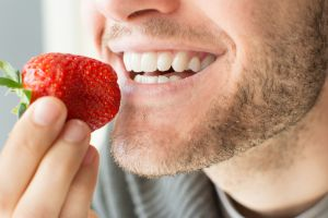 strong teeth biting strawberry